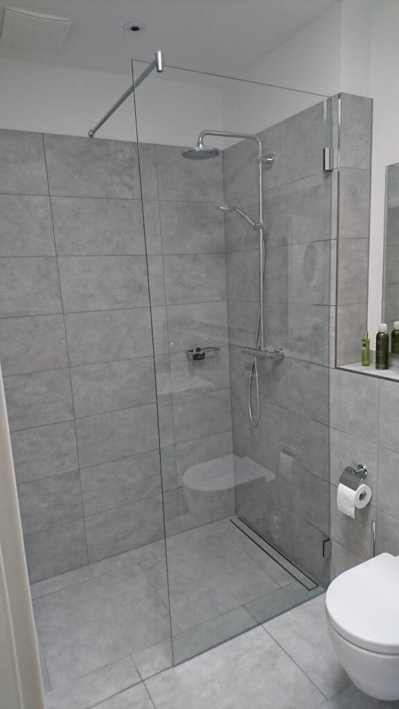 Glasdusche im grauen Badezimmer