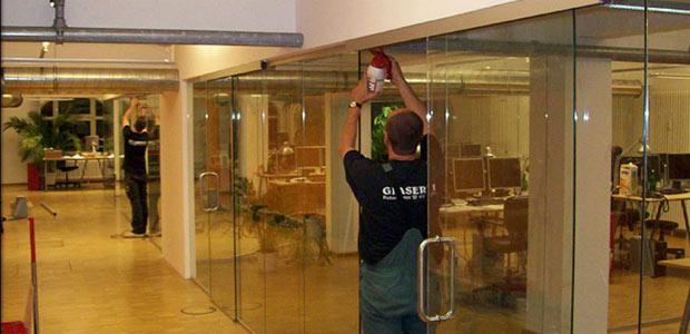 Glaser der Glaserei Thiel in Berlin beim Einbau einer Glastrennwand