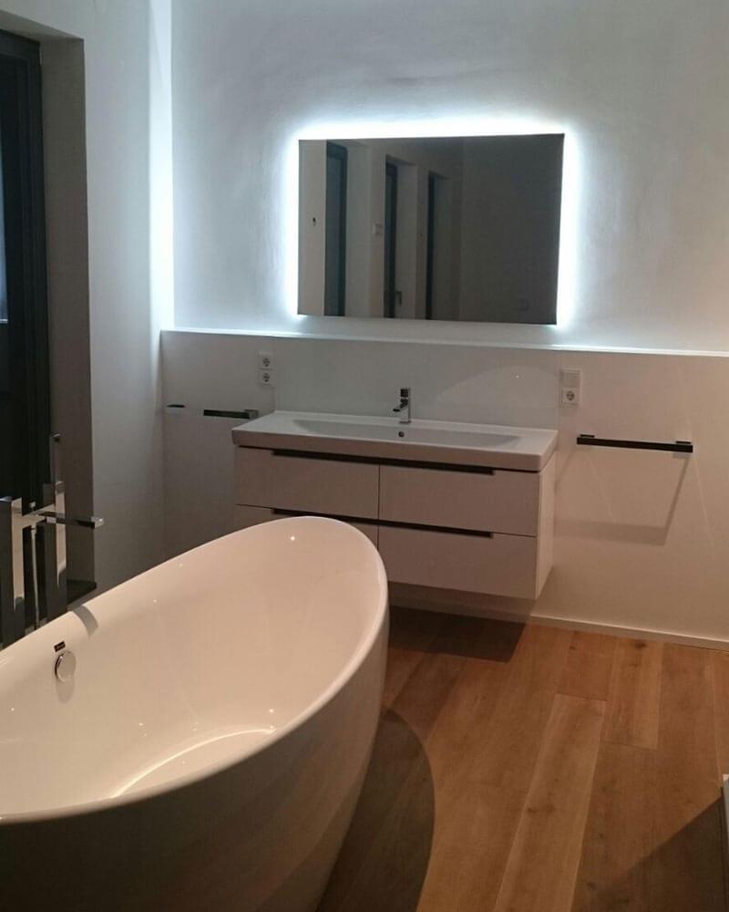 Badewanne und Waschbecken mit beleuchtetem Spiegel