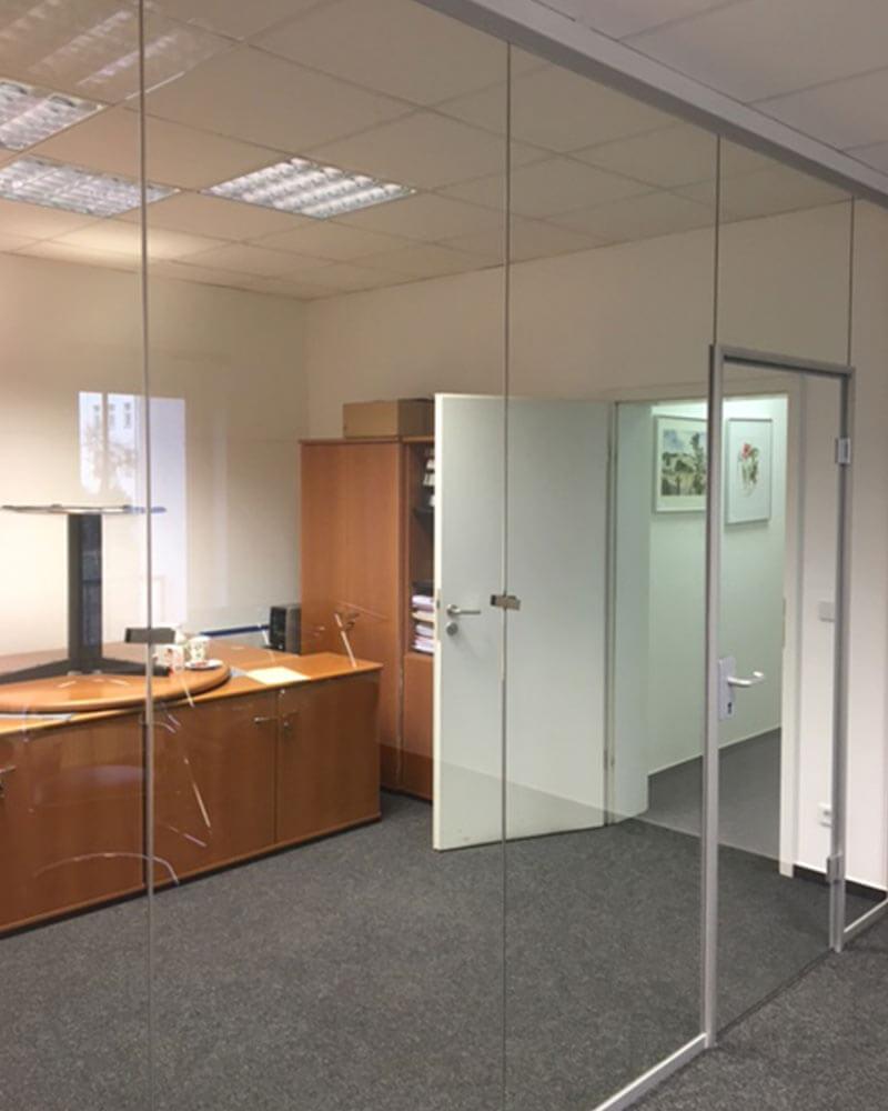 Große Glaswand mit Glastür als Raumtrennung