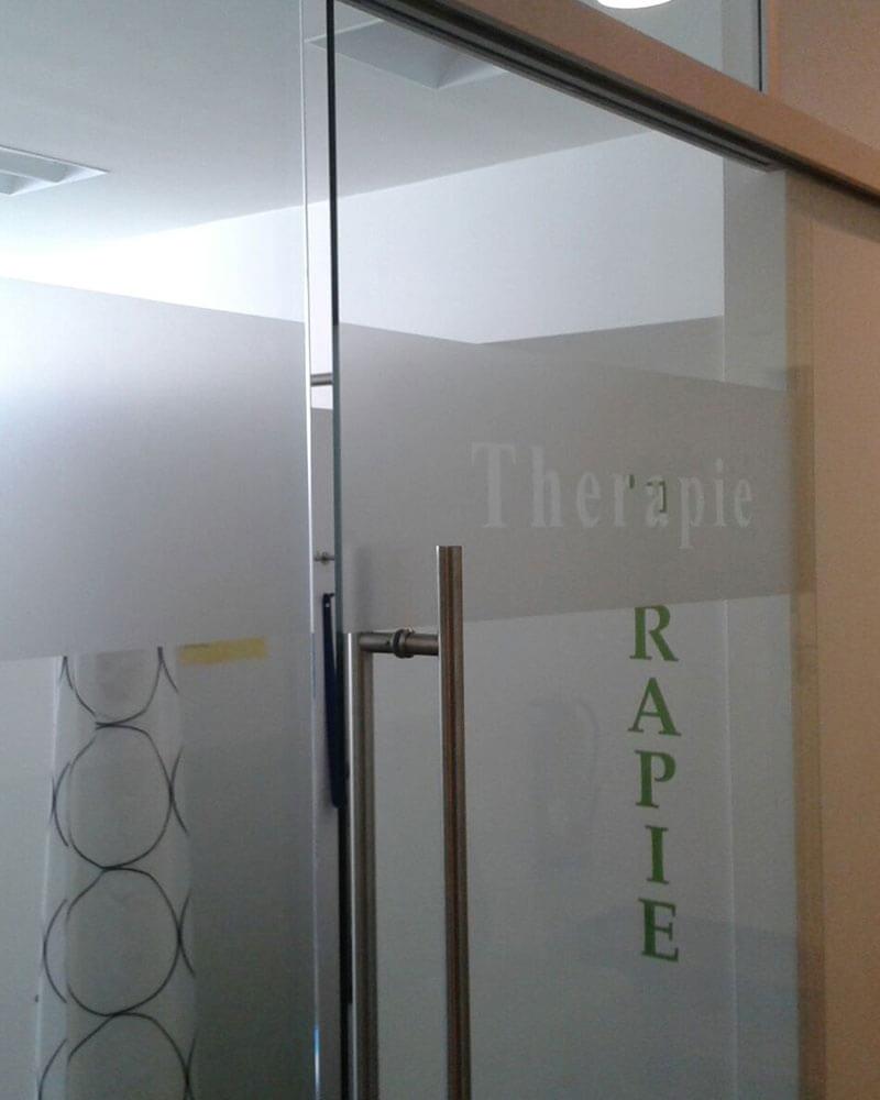 Glastür mit Beschriftung für eine Praxis